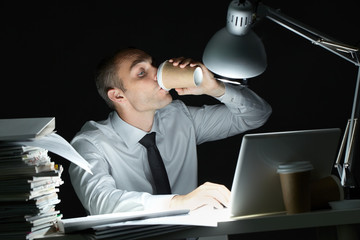 Businessman drinking coffee at desk at night