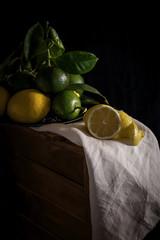 Fresh ripe citrus. Lemons, limes on dark background