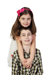 Little girl embraces boy from behind isolated on white background - love and friendship concept