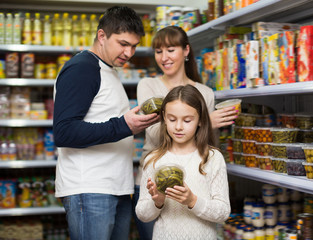 Family of three purchasing canned food