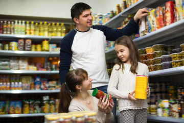 Happy family of three buying canned food
