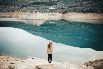 Back view of blonde woman in hat at lake