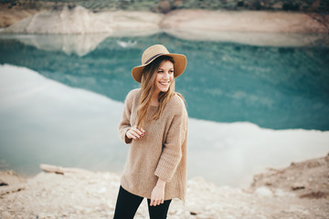 Cheerful woman in hat against of lake