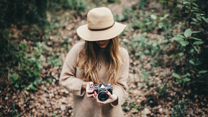 Stylish woman in hat with film camera