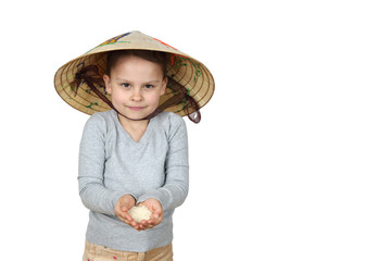 Little Asian girl in Vietnamese hat holds handful of rice in hands isolated on white background with copy space for advertising or text message