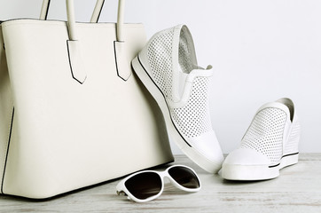 White ladies handbag, shoes and sun glasses on a light backgroun