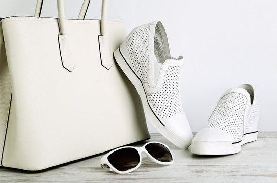 White ladies handbag, shoes and sun glasses on a light backgroun