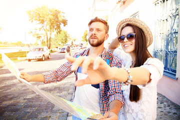 Happy couple walking outdoors sightseeing and holding map
