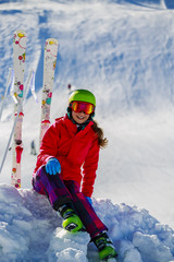 Girl sitting on the fresh powder snow at sunny day in mountains.