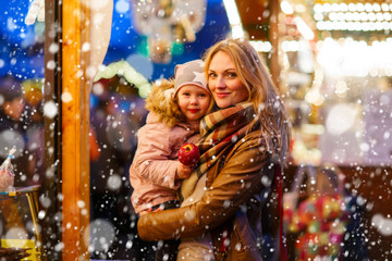Mother and little daughter on Christmas market