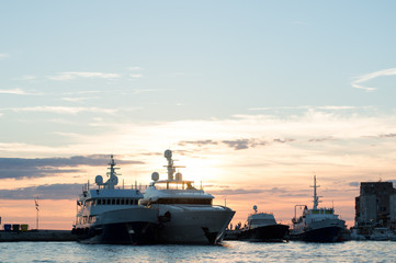 luxury boats and yachts parked in marine at sunset