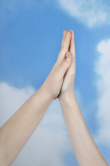 Two teenage hands palm to palm on cloudy blue sky background - friendship and togetherness concept