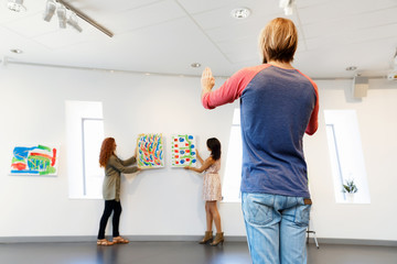Young artists in gallery hanging painting on walls