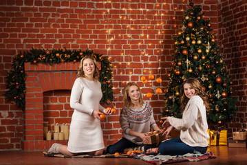 three pretty women open gifts near christmas tree