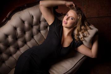 elegant woman is posing in the armchair