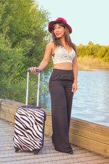Beautiful young woman posing with a trolley on a bridge over a lake.