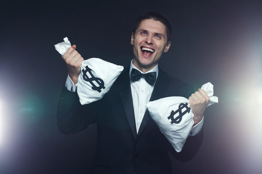 Portrait of mad businessman with two money bags laughing hysterically