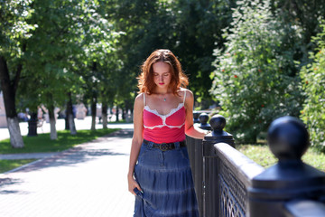 Portrait of a young attractive tourist woman leaning on a black railing,. outdoors park Beautiful woman, lifestyle.