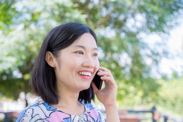 Beautiful asian woman talking with friend by smart phone