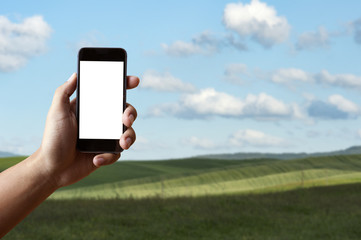 Man's Hand Holding Blank screen Mobile-phone with Blurred green field Meadow  of tuscany background