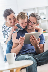 a cheerful family has fun together by playing on a tablet