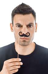 Young man with paper moustaches making faces isolated on white b
