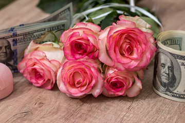 beautiful roses with money on desk