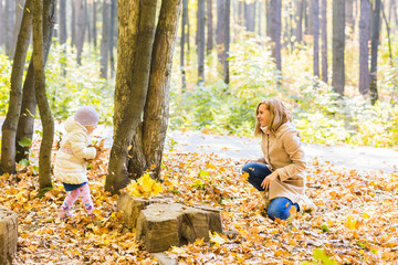 happy family mother and child girl playing throw leaves in autumn park outdoors