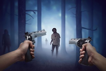 Man hand holding two gun and ready to shooting walking zombie