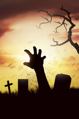 Silhouette corpse raising hands from his grave on the cemetery