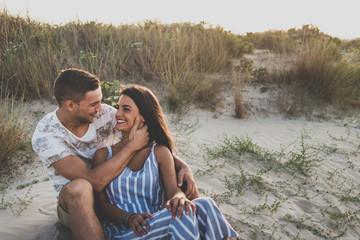 Cheerful couple sitting on beach