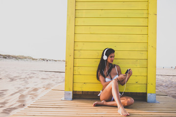 Woman listening to music on the phone on the beach
