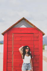 Smiling woman in sunglasses and cowboy hat against red changing room on beach