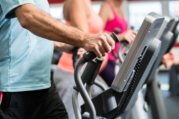Senioren trainieren am Crosstrainer im Fitnessstudio mit Fitnesstrainer