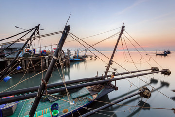 Fishing boats in harbour with sunset