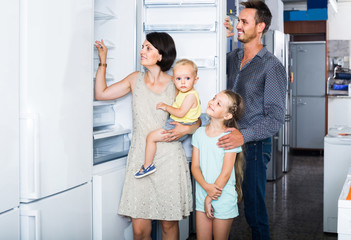 family of four shopping new refrigerator in home appliance store