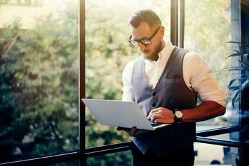 Stylish Bearded Businessman Wearing Glasses White Shirt Waistcoat Working Modern Laptop Holding Hands Near Panoramic Window.Man Work Office Startup Project.Sunlight Effect.Blurred Background.