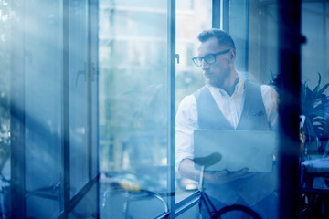 Young Bearded Businessman Wearing Glasses White Shirt Waistcoat Holding Modern Laptop Hands Looking Panoramic Windows.Man Working Office Startup Project Workplace.View Through Window.Blurred.