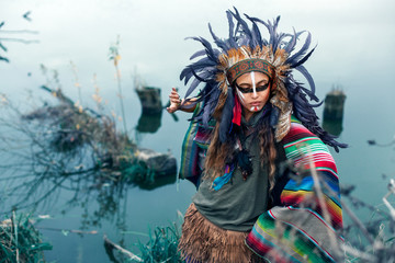 Beautiful girl dressed in native American Indian clothes, with paint face camouflage and headdress with black feathers and fur dancing in front of lake in summer