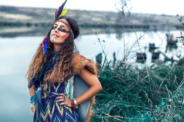Beautiful Native American Indian girl dressed in colorful dress, with paint face camouflage and headdress with feathers and fur smiling with white teeth in front of lake