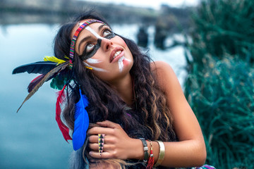 Beautiful Native American Indian girl dressed in colorful dress, with paint face camouflage and headdress with feathers and fur looking up in the sky and smiling in front of the lake, posing on camera