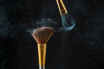 Make-up brushes with powder isolated on black background