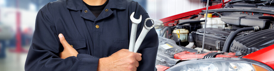 Hands of car mechanic with wrench in garage. Wall mural
