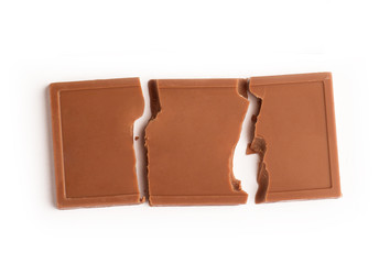 Broken milk chocolate bar on white background