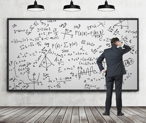 Man in suit looking at whiteboard with formulas