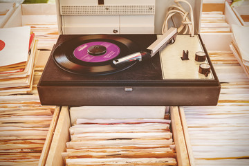 Old record player on top of used vinyl lp records