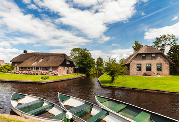 Small Dutch canal boats in front of old houses in Giethoorn