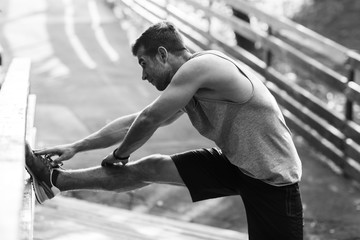 Young athlete doing stretching exercises, black and white photo