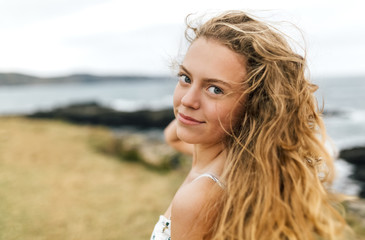 Portrait of smiling blond teenage girl with blowing hair at the coast