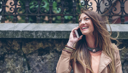 Happy woman on cell phone outdoors